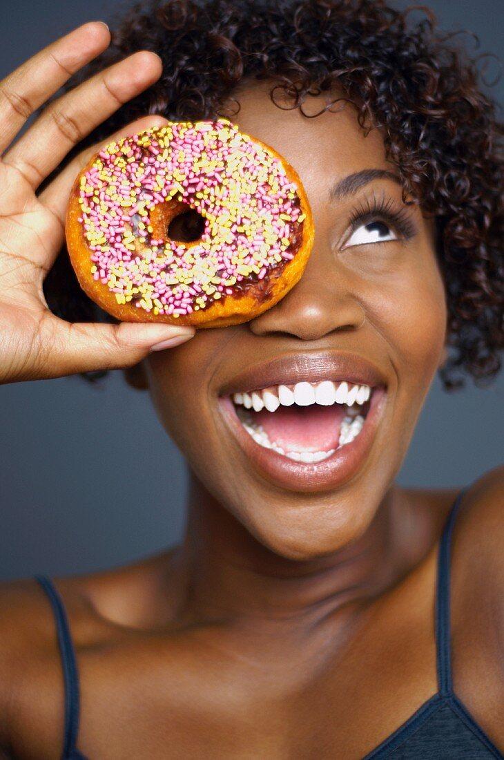 Dunkelhäutige Frau hält sich Donut vor das Auge