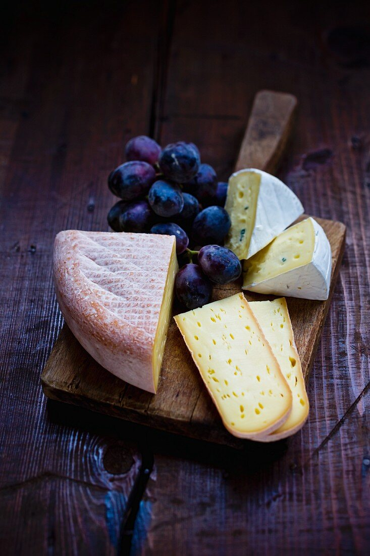 A cheese board with red grapes