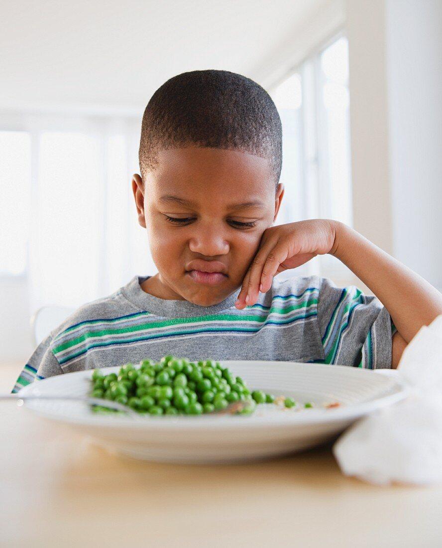 African American grimacing at plate of peas