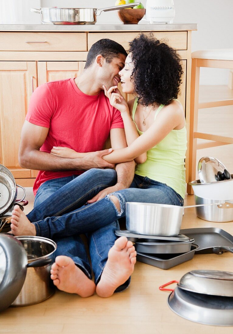 Couple kissing on kitchen floor surrounded by pots and pans