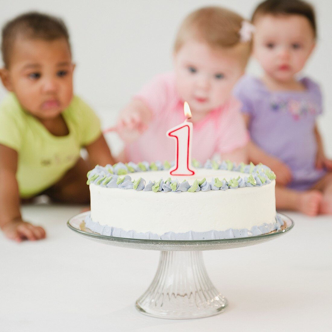 Babies looking at first birthday cake