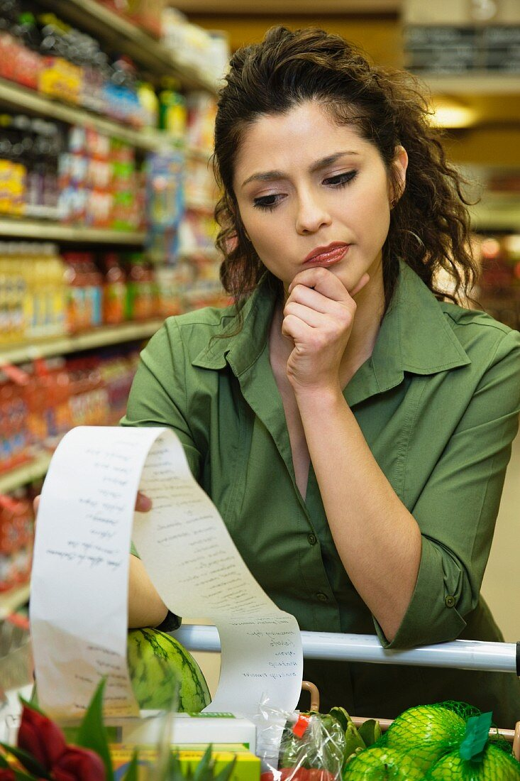 Hispanic woman reading list in grocery store