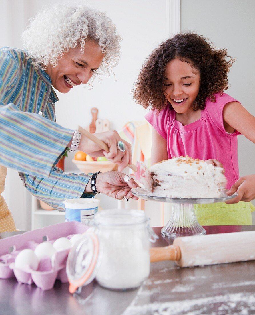 Grossmutter und Enkelin beim Dekorieren einer Torte