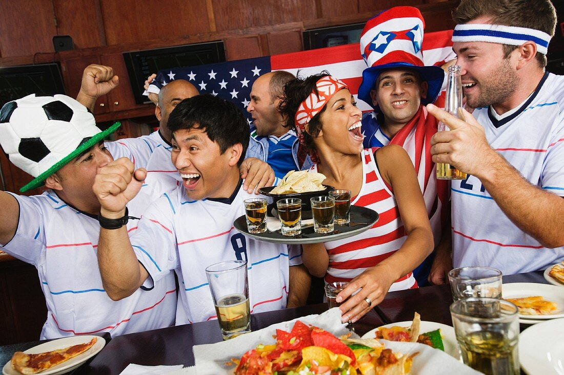 Sports fans drinking and eating in sports bar