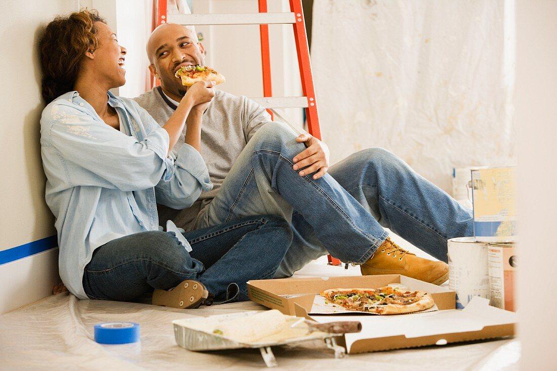 Afrikanisches Paar macht Mittagspause beim Ausmalen der Wohnung