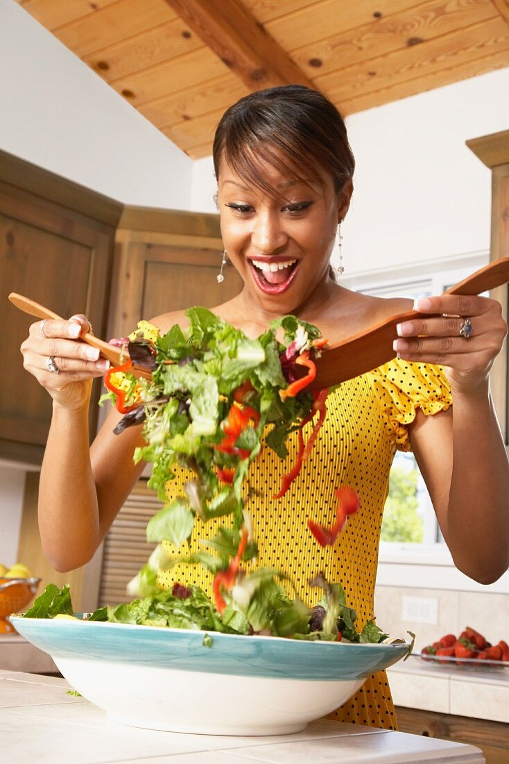 A woman mixing salad in a bowl