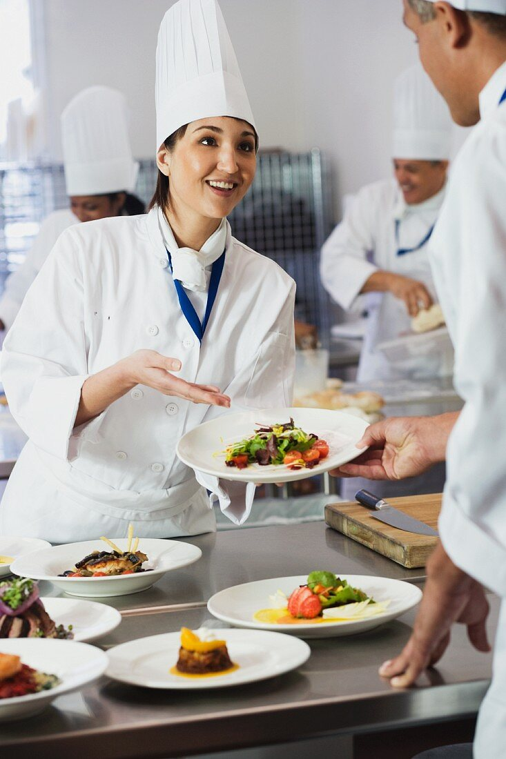 Asian female chef handing plate of food