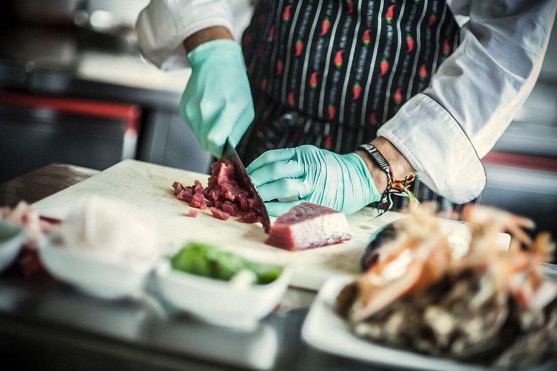 A chef cutting up tuna fish for tuna tartare