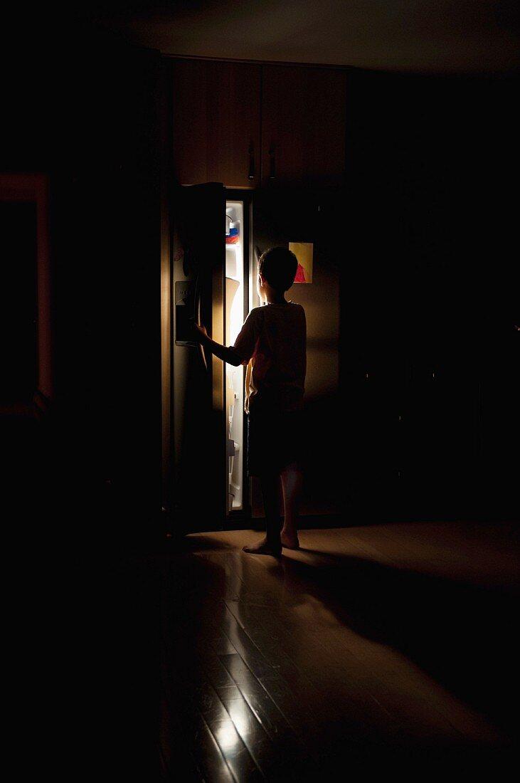 Boy looking in refrigerator in dark kitchen