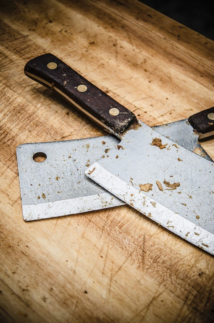 Two Meat Cleavers Covered with Bits of Meat on Wooden Cutting Board