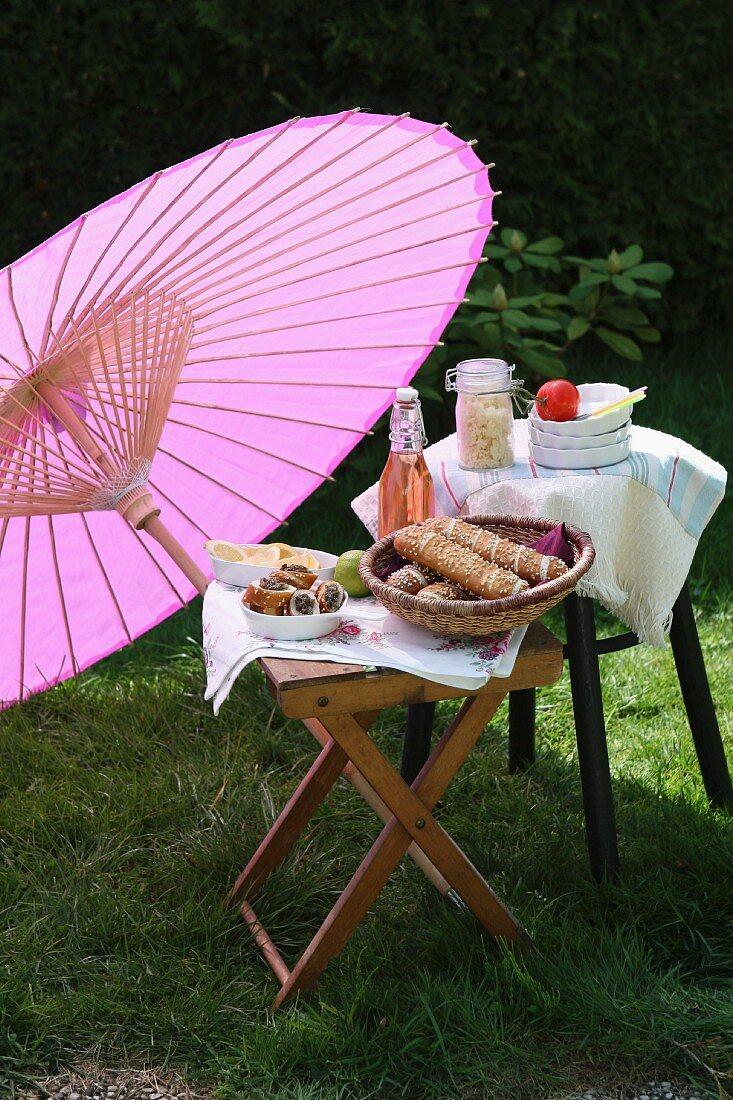 Picnic of bread rolls and lemonade under Oriental paper parasol in garden