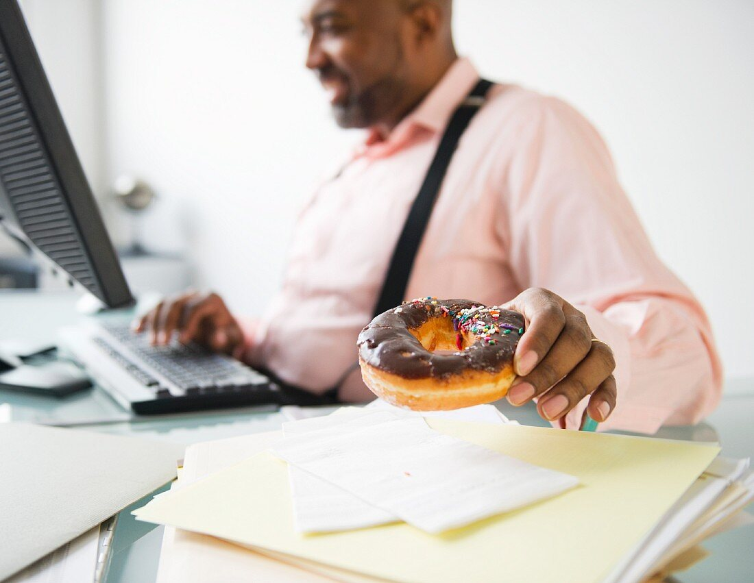 African American businessman eating donut at desk