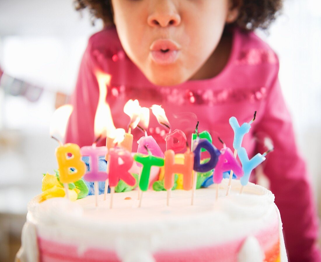 African American girl blowing out birthday candles