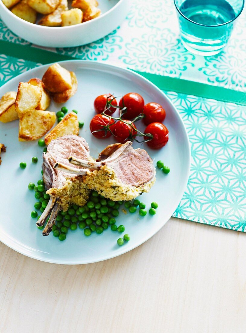 Saddle of lamb with a herb crust, served with peas, potatoes and tomatoes