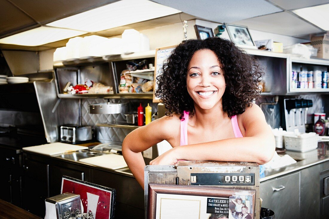 A young woman leaning on the till in a snack bar