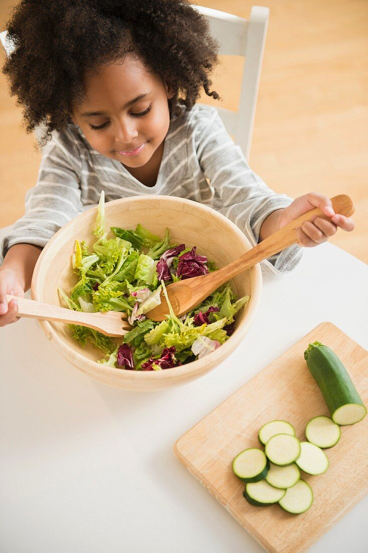 An African-American girl sitting at a table with a bowl of salad