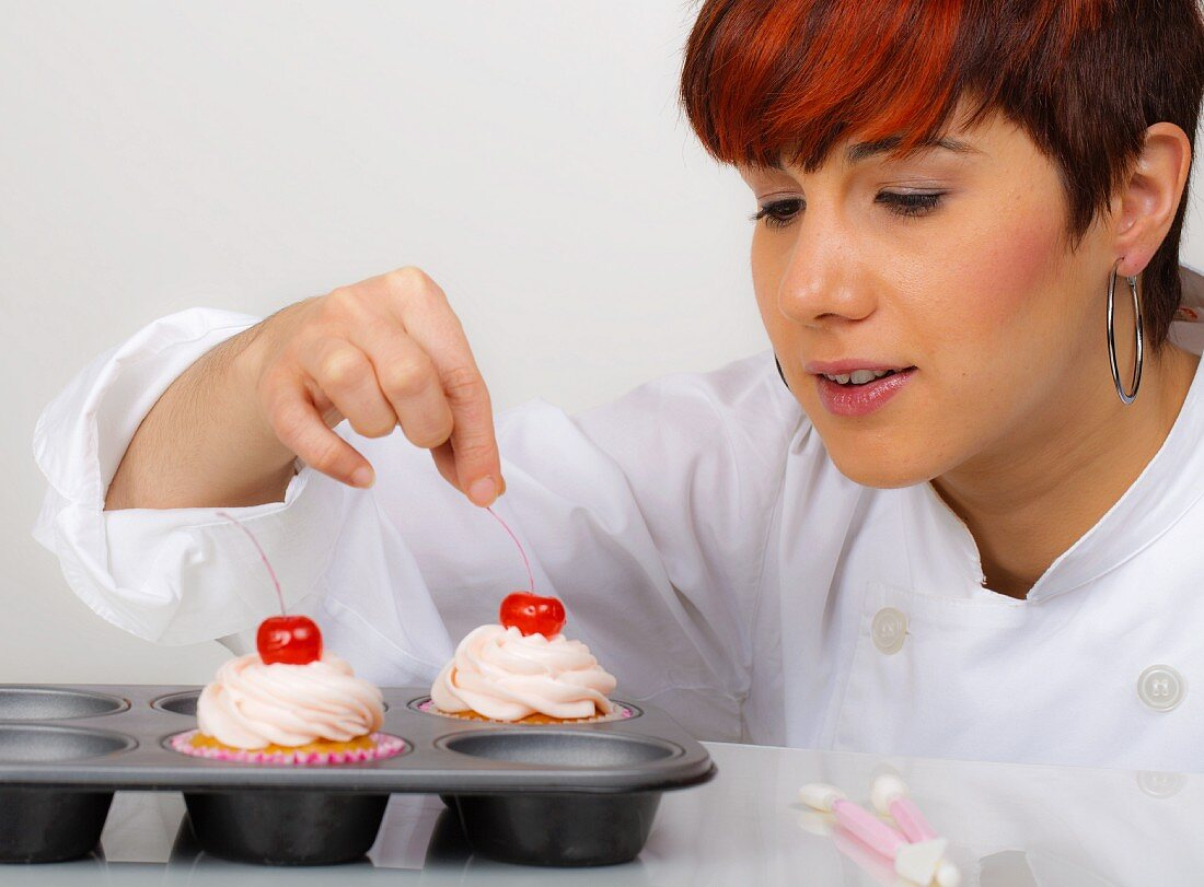 A woman decorating cupcakes
