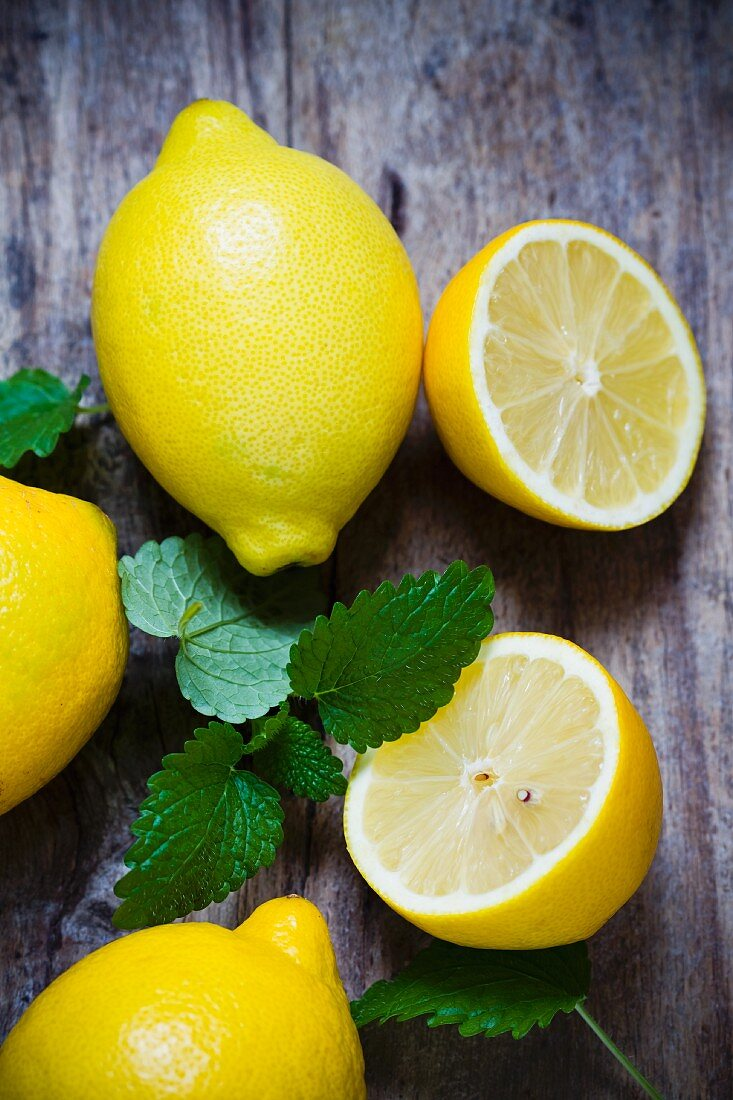 Fresh lemons and lemon balm on a wooden surface