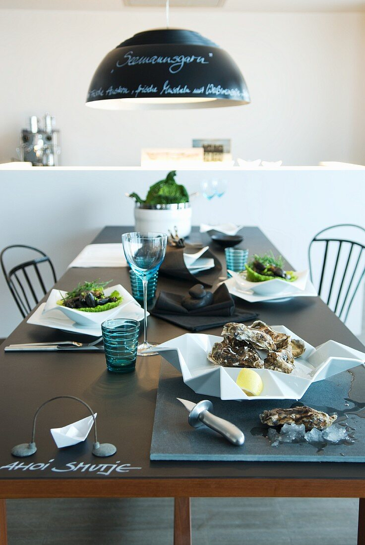 Stylishly set table with oysters on white, designer china plates and blue drinking glasses