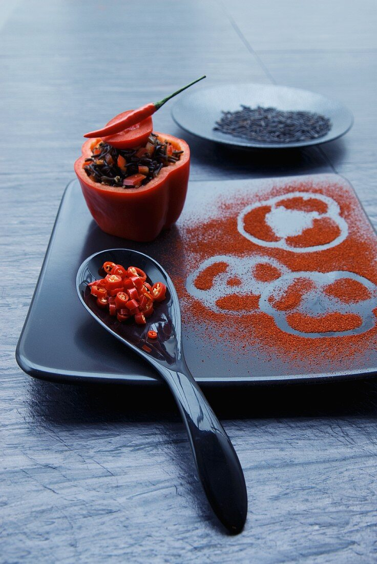 A stuffed pepper filled with wild rice, chilli and tomatoes with a spoonful of chilli rings and a black plate with paper prints in paprika powder