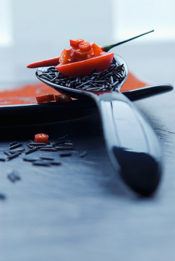 Wild rice on a spoon with tomatoes, chilli and chilli rings