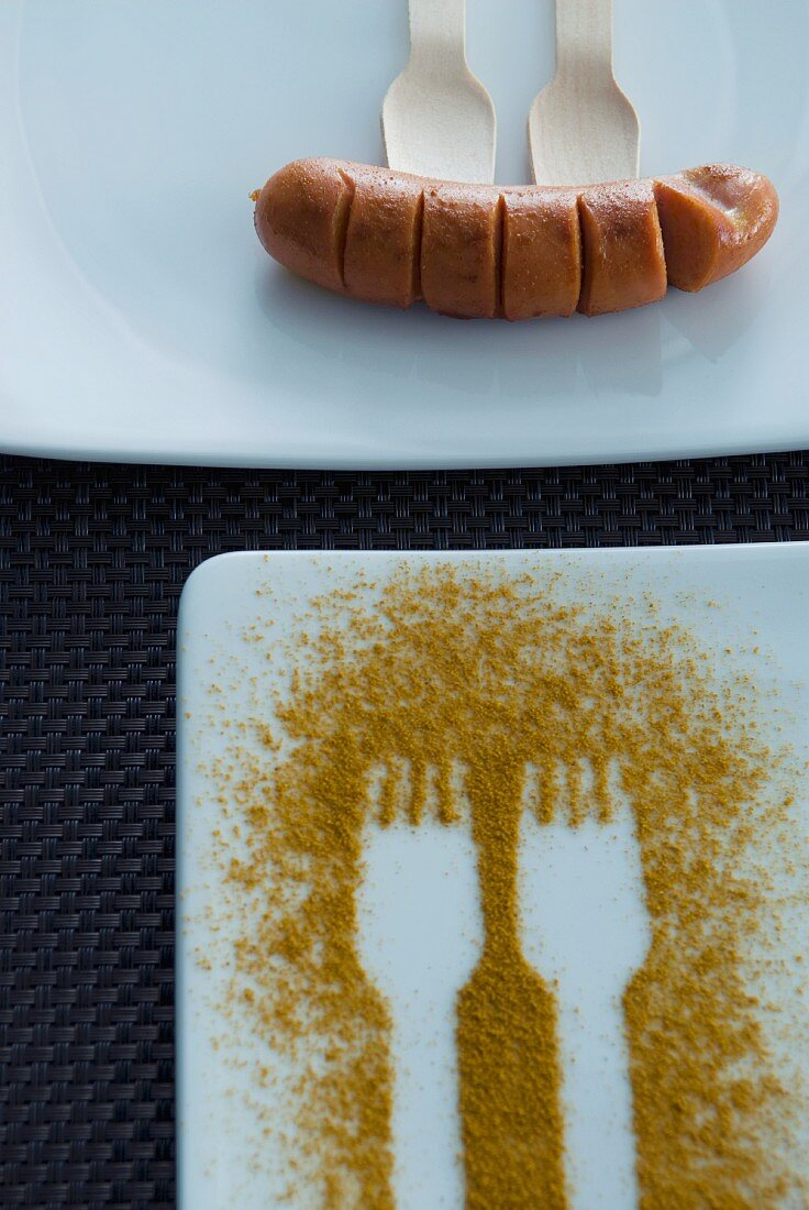 Fork prints in curry powder on a plate and a sausage