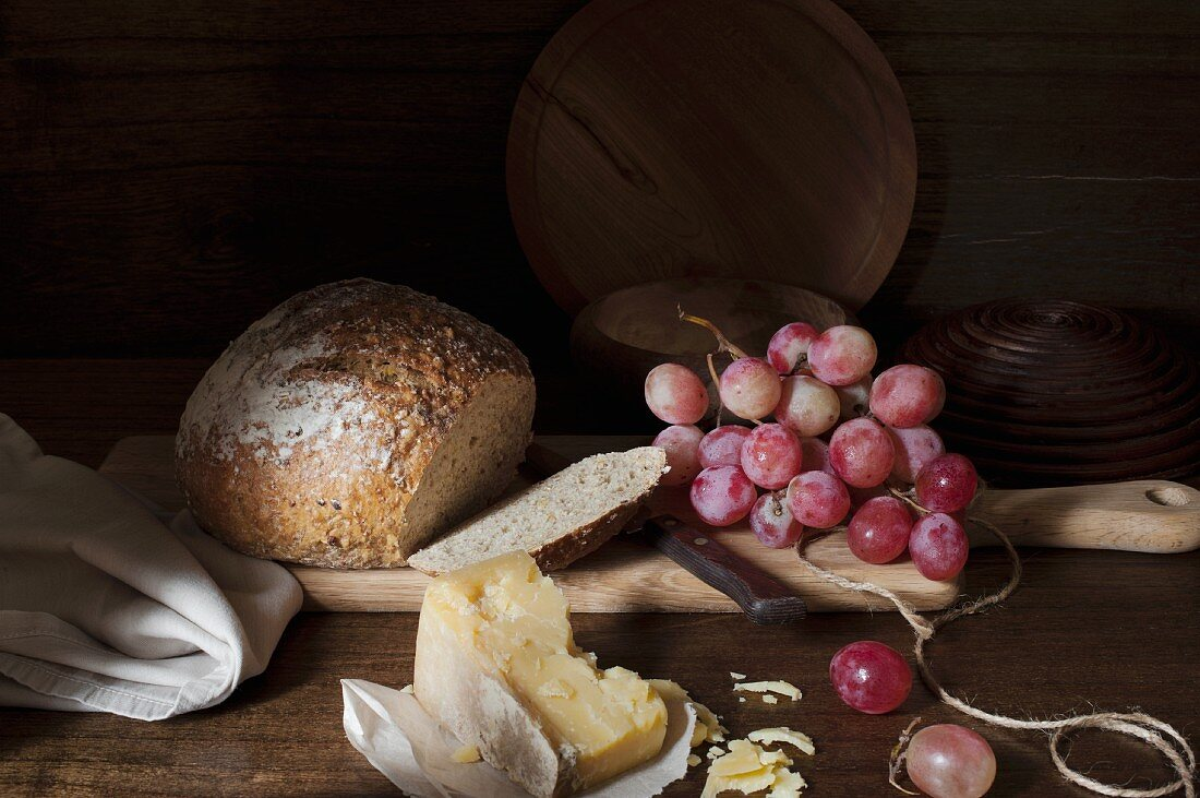 Loaf of bread sliced removed with a vintage cheese and a bunch of grapes on a wooden chopping board.