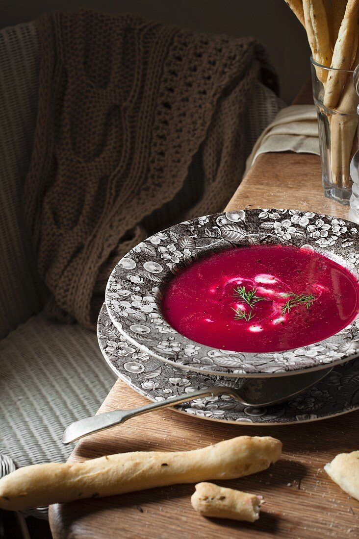 A bowl of beetrot soup with sour cream, dill and bread.