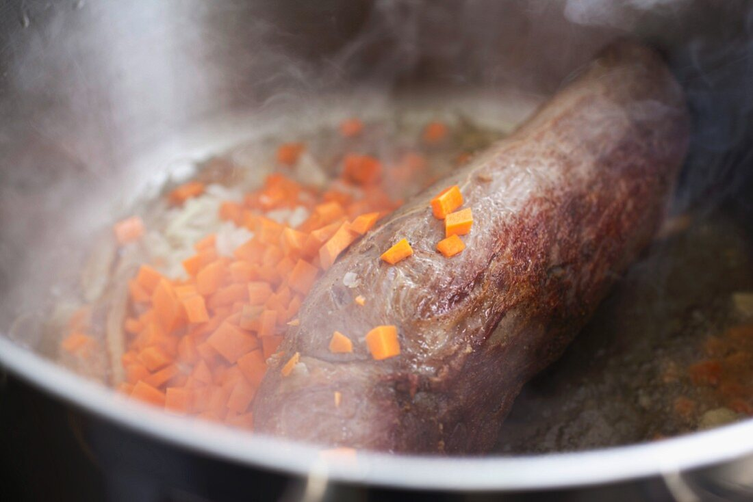 pieces of carrots and onions frying with a tenderloin beef in a pot, for a typical Czech dish called Svickova
