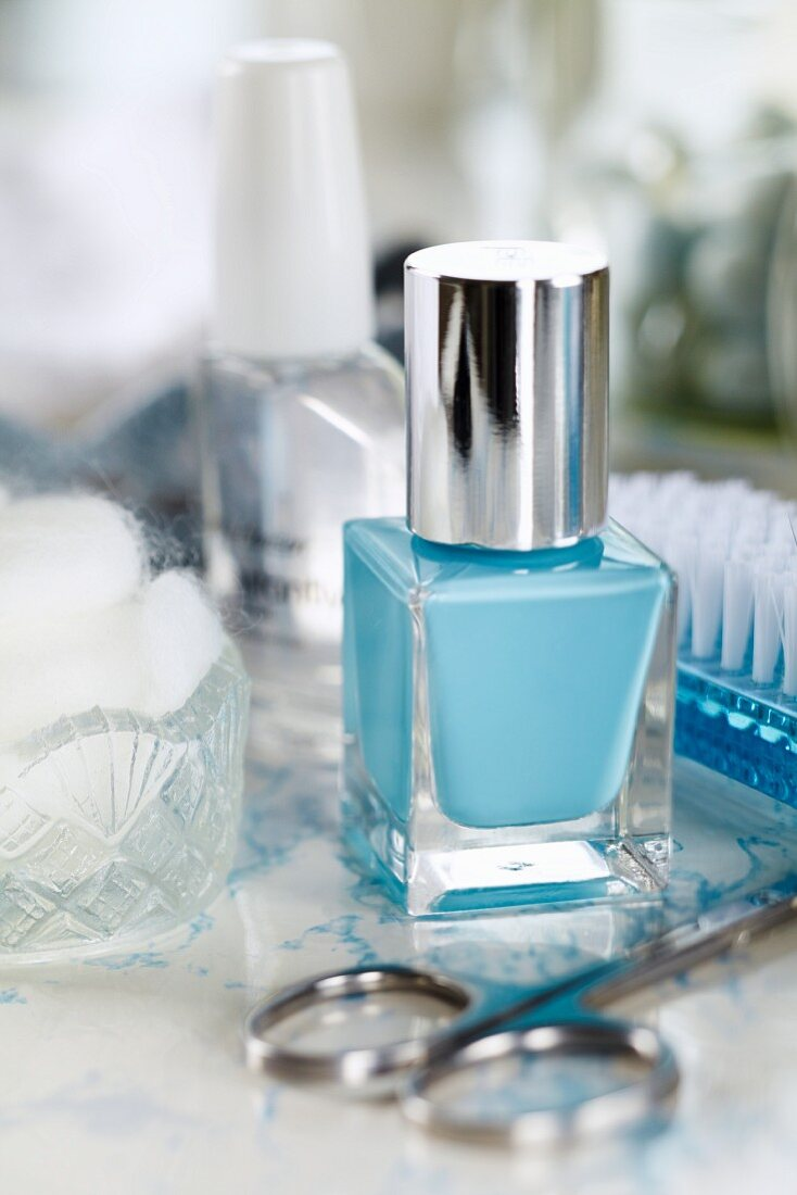 A bottle of blue nail varnish, nail scissors and beauty utensils