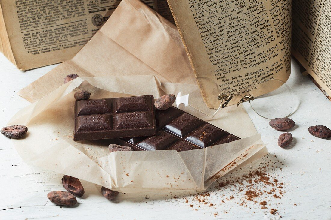 Dark chocolate and chocolate beans with vintage book