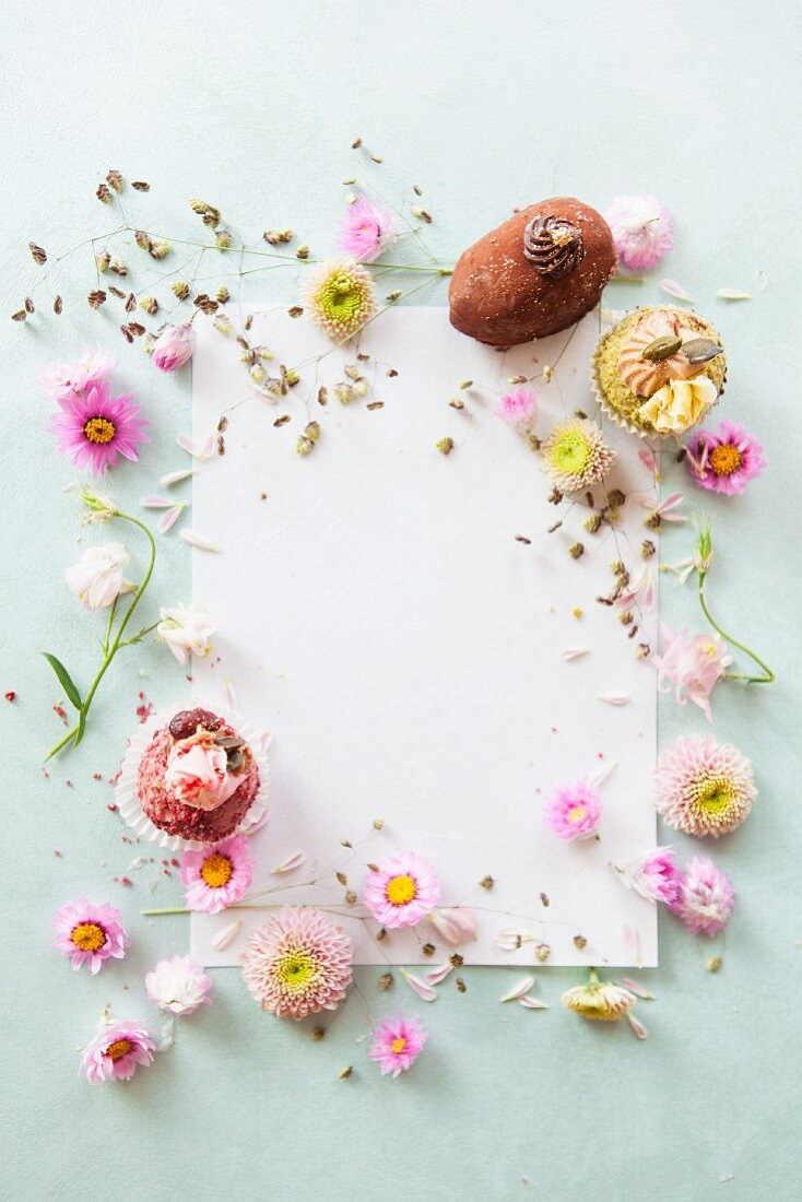 A sheet of writing paper decorated with pralines and flowers (seen from above)