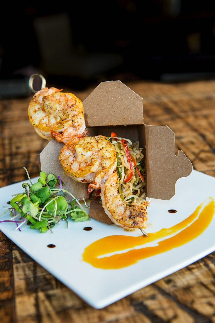 A grilled prawn kebab with sauce