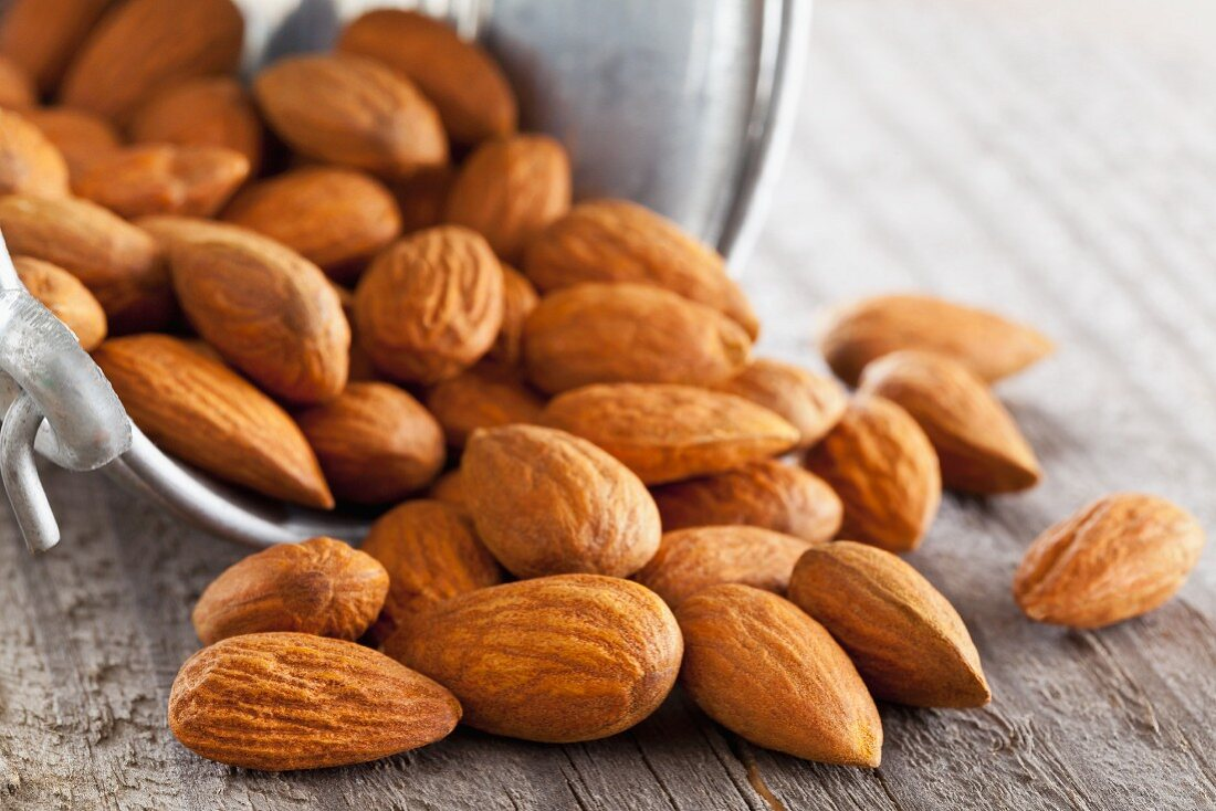 Whole almonds falling out of a metal bucket