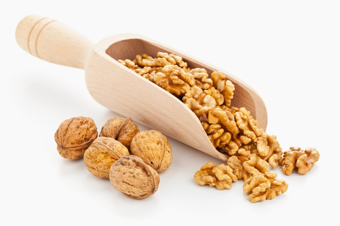 Walnuts on a wooden scoop with whole walnuts next to it