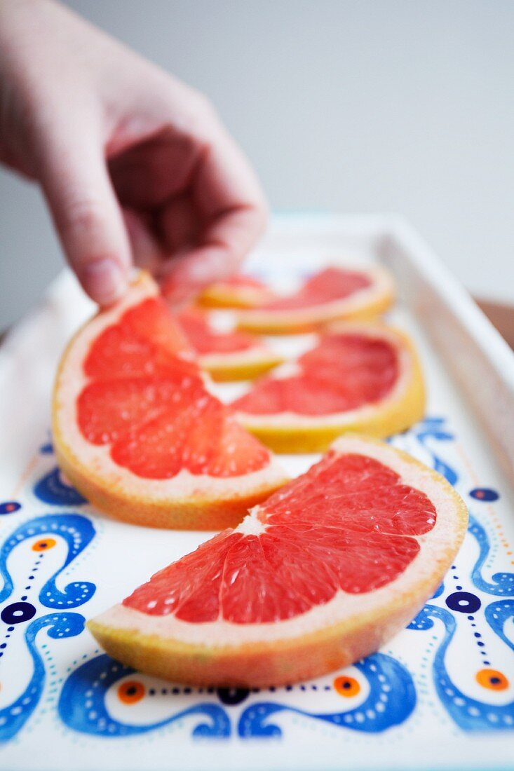 A hand reaching for a slice of grapefruit