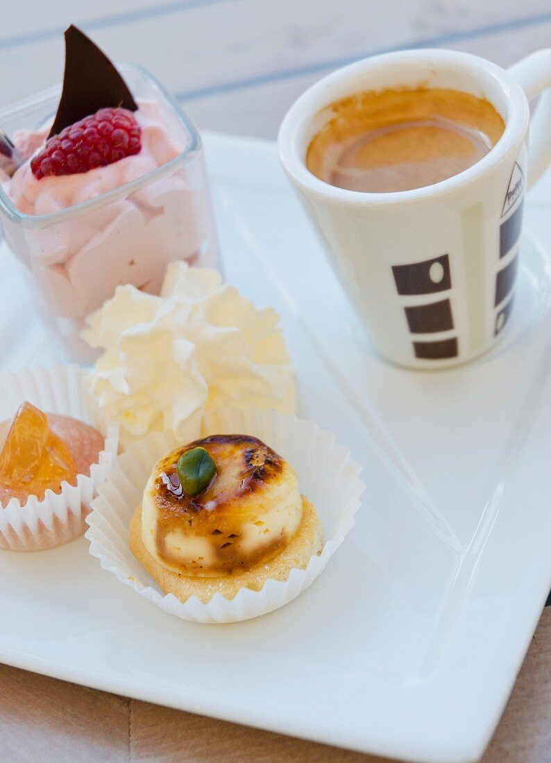A cup of coffee and a selection of desserts on a porcelain plate