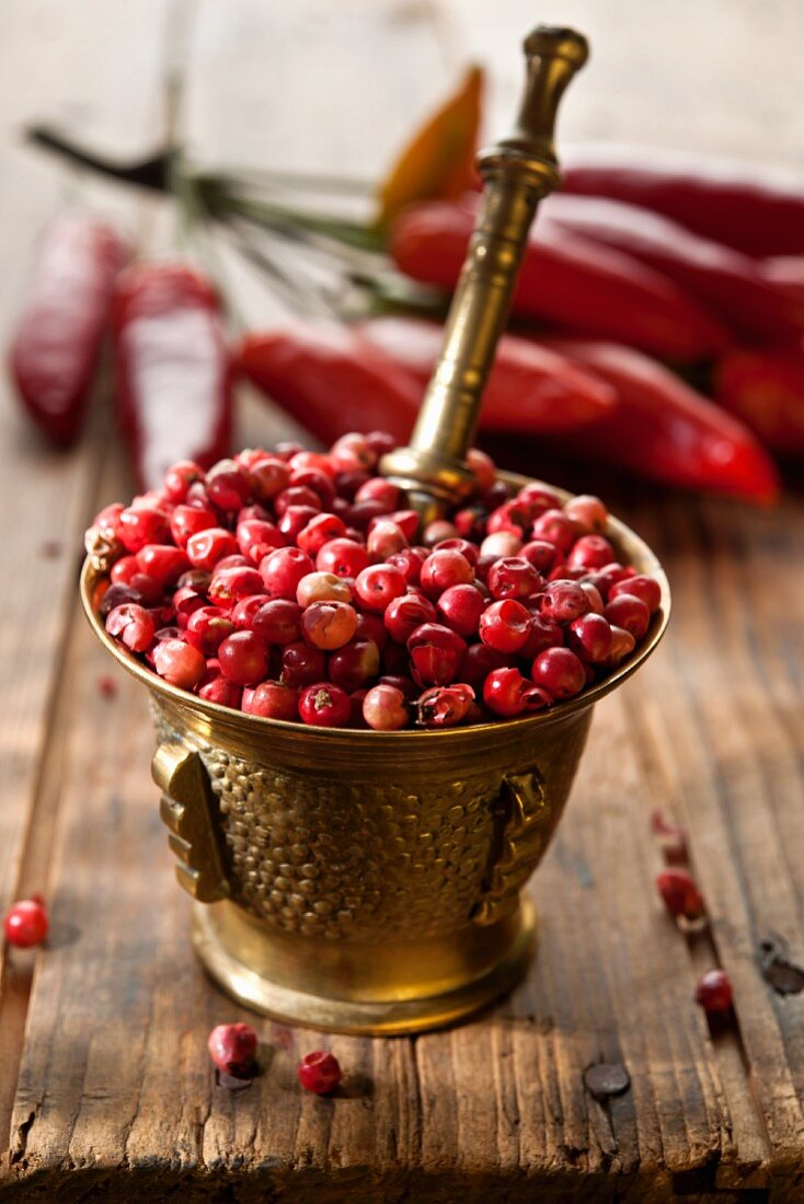 Pink peppercorns in a mortar with red chilli peppers in the background on a wooden table