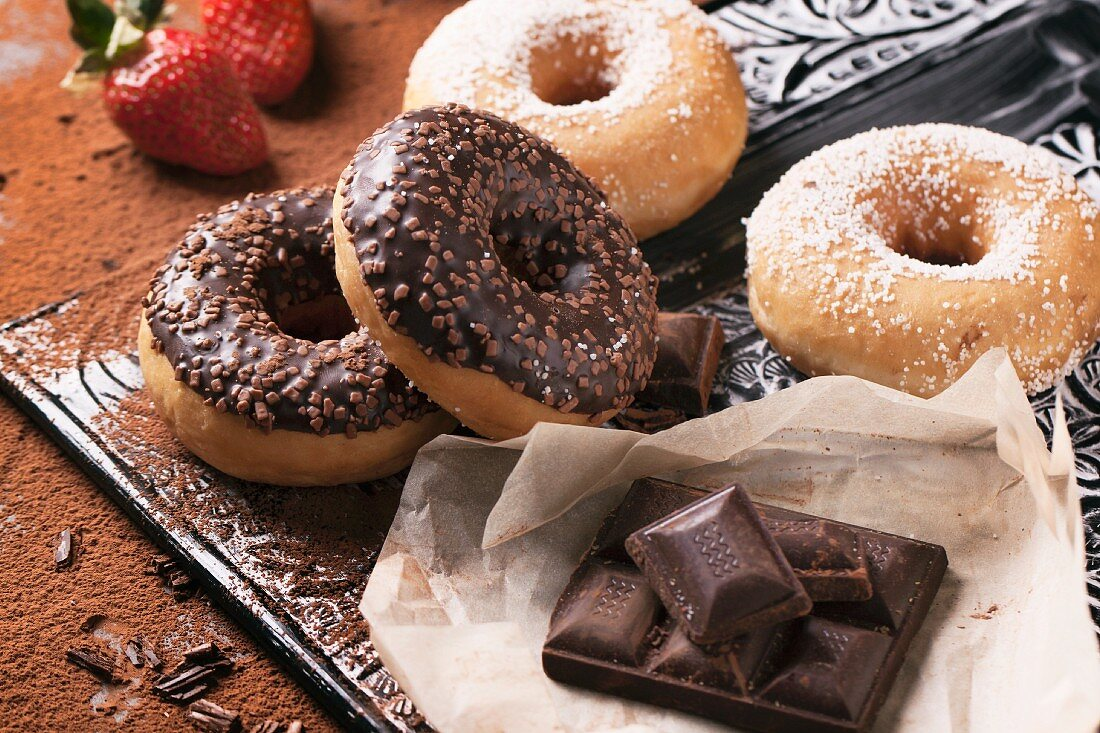 Chocolate glazed doughnuts, sugared doughnuts and dark chocolate on a tray with strawberries in the background