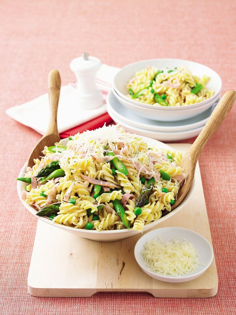 Pasta salad with ham, peas, green asparagus and parmesan