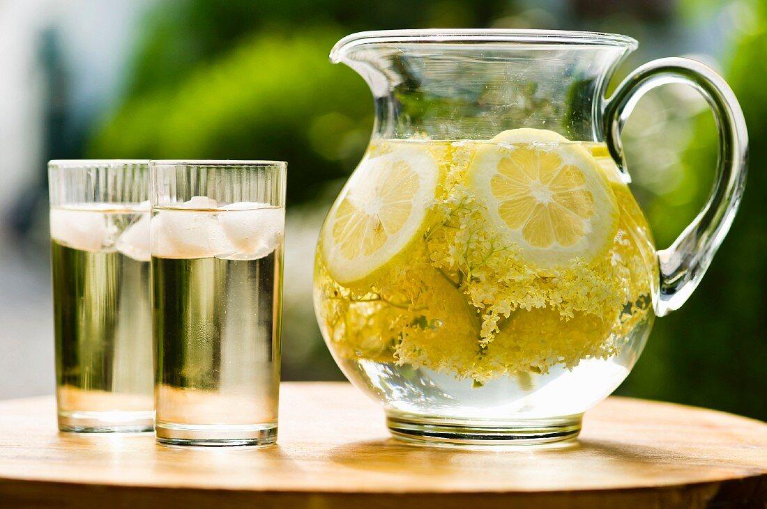Elderflower juice with lemon in a glass jug and in glasses