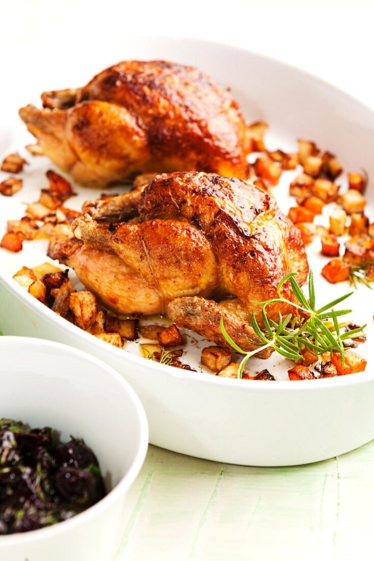 Two roast chickens with root vegetables and rosemary