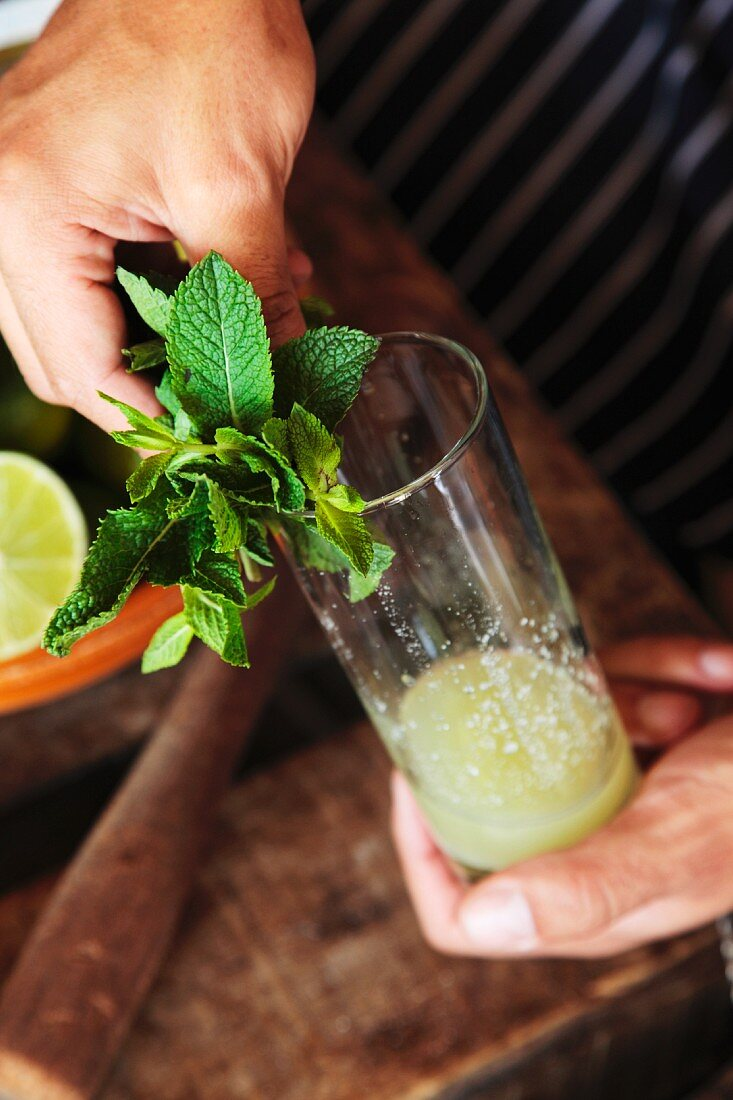 A mojito being made (mint being arranged on the edge of the glass)