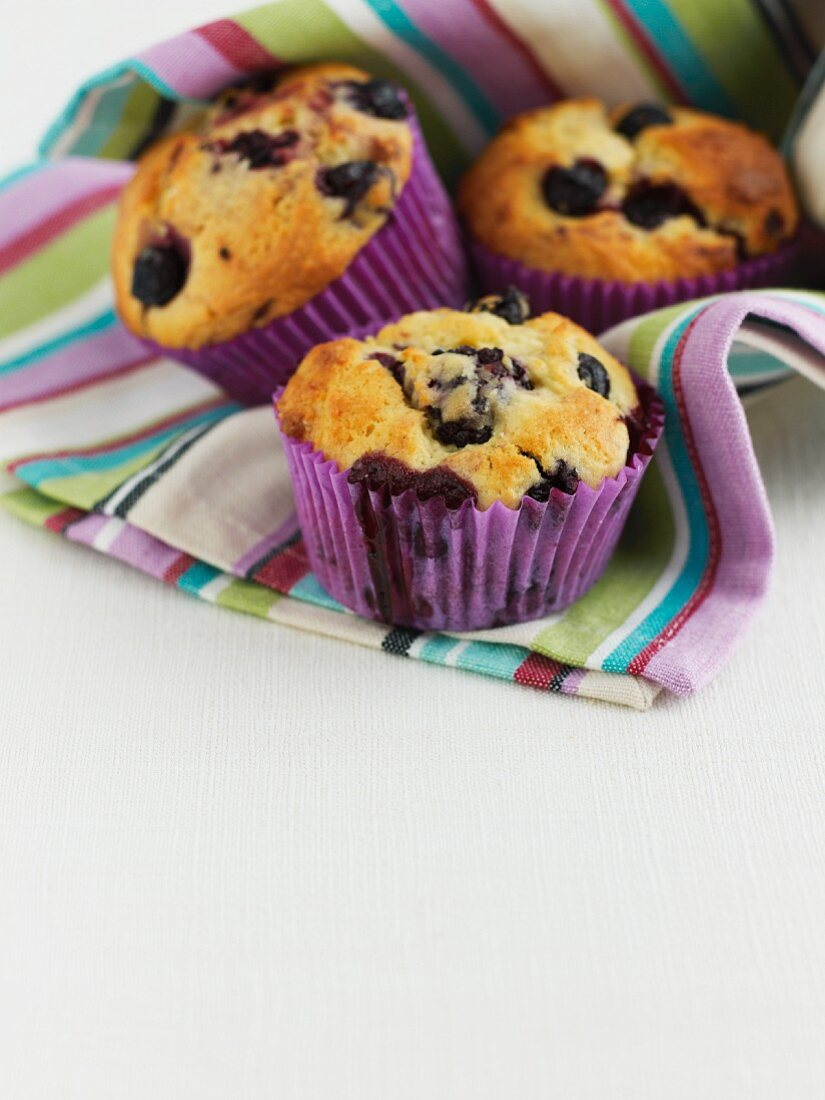 Three blueberry muffins in a stripped cloth