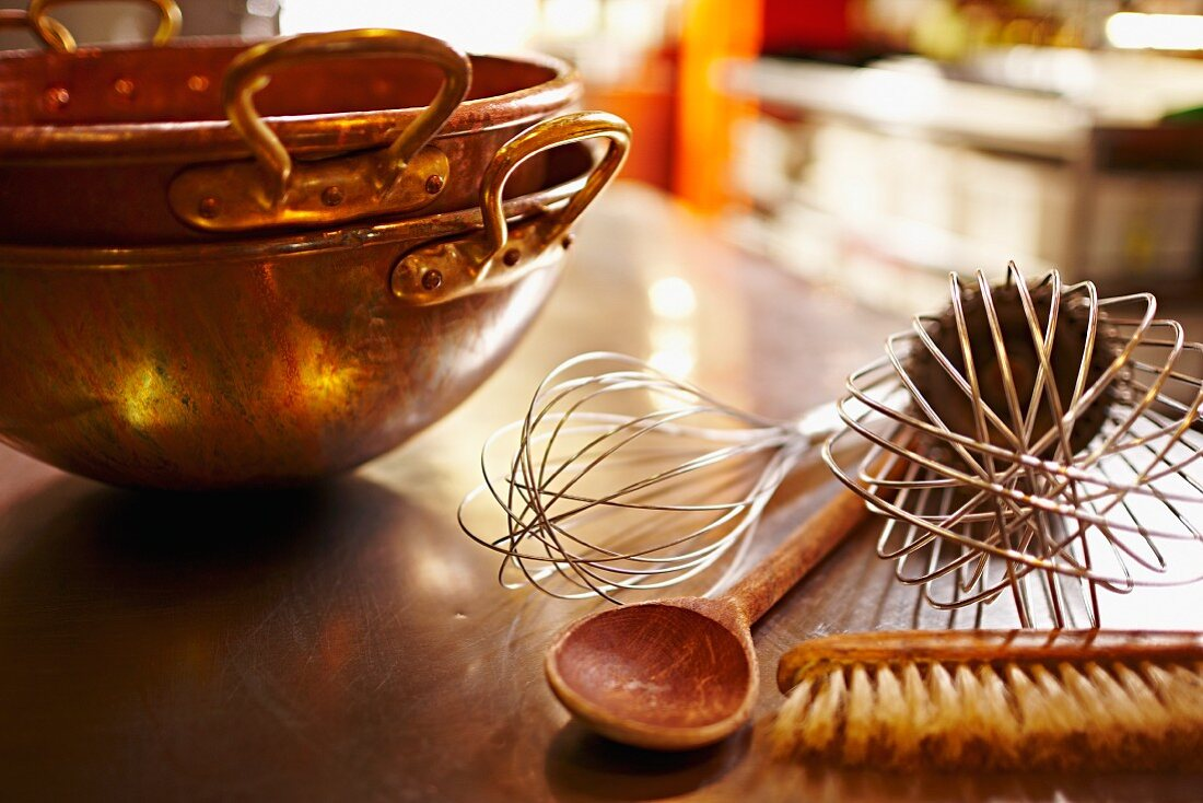 A copper kettle, whisks, a wooden spoon and a brush