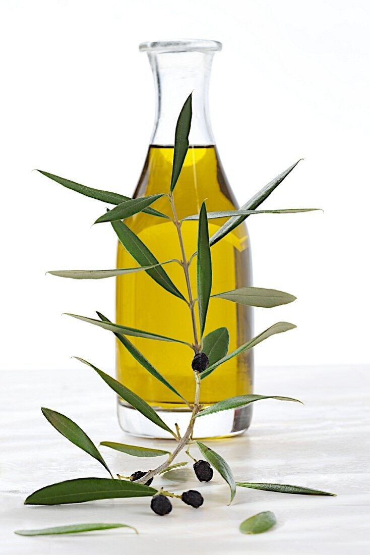 A bottle of olive oil with an olive sprig in the foregroud