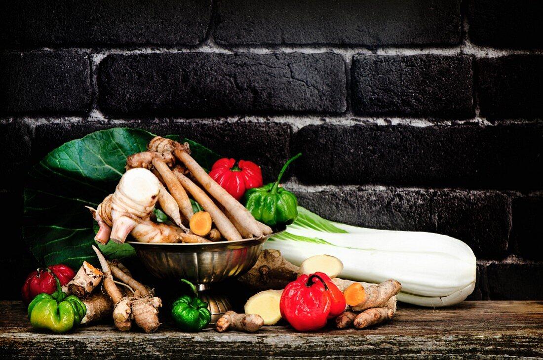 An arrangement of vegetables on a wooden board: bok choy, galangal, curcuma and Scotch Bonnet chillis
