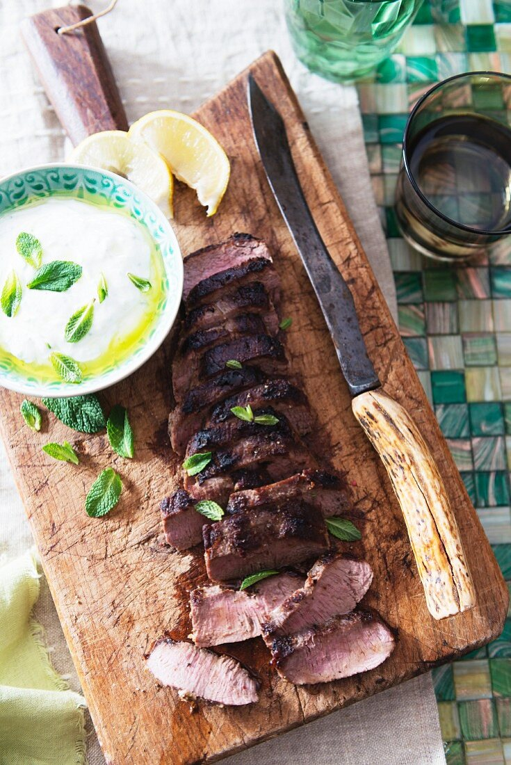 Roast lamb with tzatziki on a chopping board