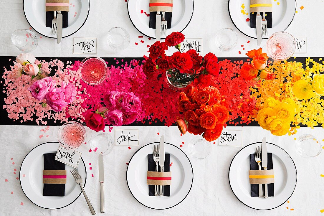 Festively set table with colour-coordinated confetti & flowers