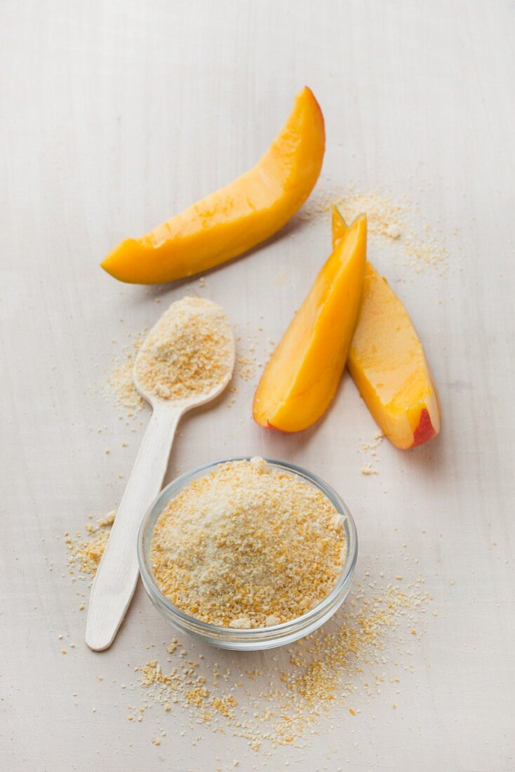 Mango fruit powder in a glass bowl and on a spoon